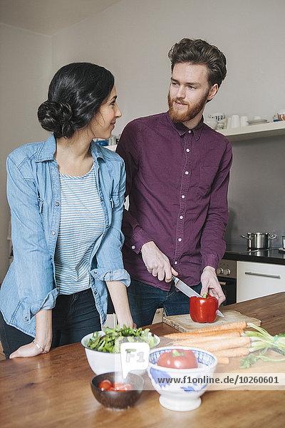 Junger Mann hackt rote Paprika  während er die Frau in der Küche ansieht.