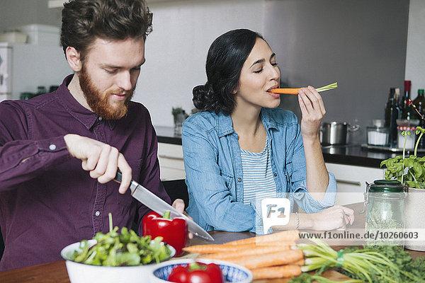 Junger Mann hackt rote Paprika neben einer Frau  die Karotte am Küchentisch isst.
