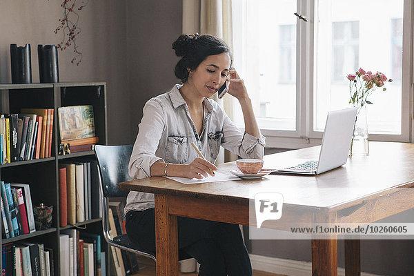 Junge Frau mit Handy und Laptop auf dem Tisch zu Hause
