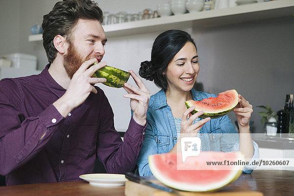 Glückliches junges Paar beim Essen von Wassermelone am Küchentisch