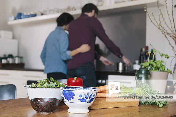 Gemüse auf Küchentisch mit Paarkochen im Hintergrund
