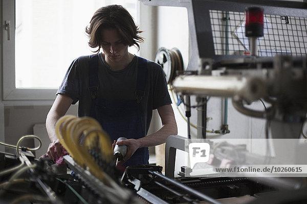 Junge Handarbeiterin Ölmaschine in der Fabrik