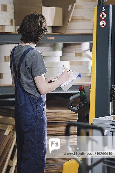 Seitenansicht des jungen Handwerkers beim Schreiben auf Papier im Lagerhaus