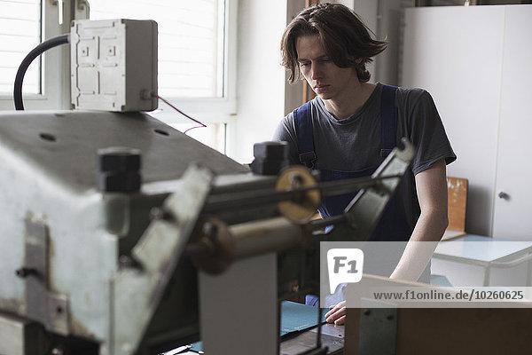 Junger Arbeiter  der die Maschine in der Fabrik bedient