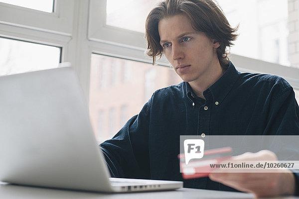 Junger Mann mit Kreditkarte und Laptop am Tisch