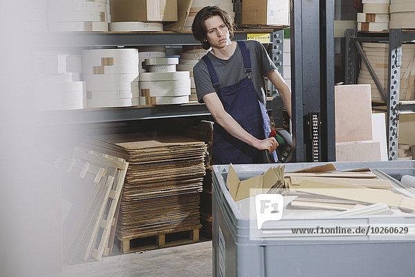 Porträt des jungen Mannes  der die Maschine in der Fabrik bedient.
