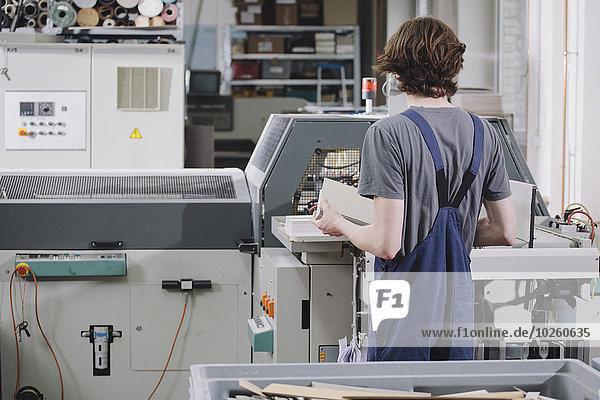 Rückansicht des jungen Mannes  der die Maschine in der Fabrik bedient.