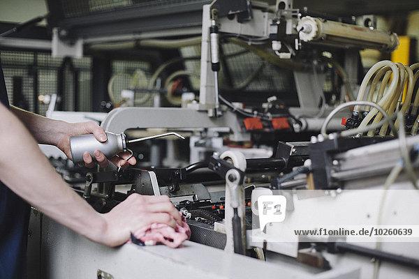Beschnittenes Bild der manuellen Arbeiter-Ölmaschine in der Fabrik