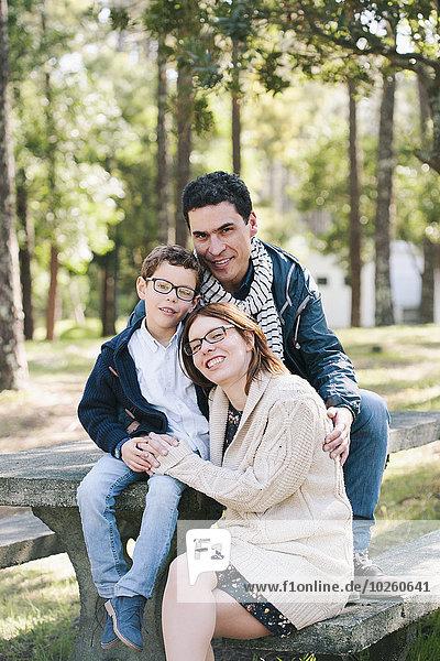 Porträt einer glücklichen Familie am Picknicktisch im Wald