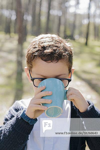 Nahaufnahme des Jungen beim Kaffeetrinken im Wald