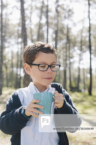 Junge mit Kaffeetasse im Wald