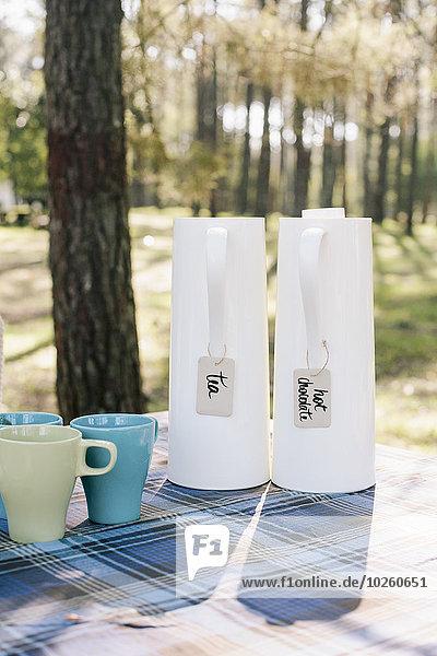Krüge und Becher auf dem Tisch im Wald