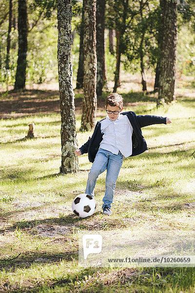 Volle Länge des Jungen beim Fußballspielen im Wald
