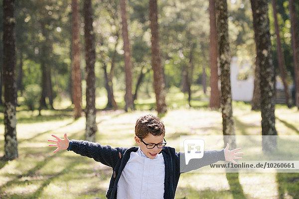 Glücklicher Junge mit ausgestreckten Armen im Wald