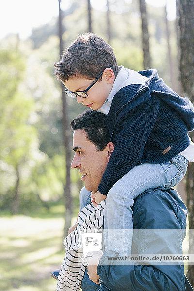 Lächelnder Mann mit Sohn auf den Schultern im Wald