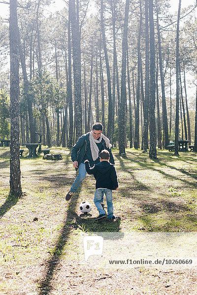Vater und Sohn spielen Fußball im Wald