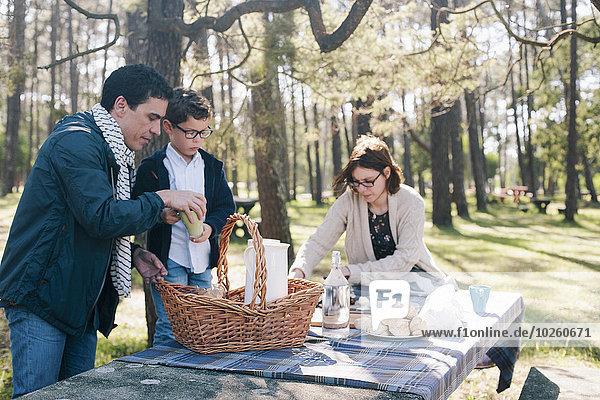 Familie bereitet sich auf das Frühstück im Wald vor