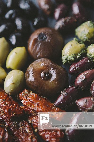 Nahaufnahme verschiedener Oliven mit Zwiebeln und sonnengetrockneten Tomaten