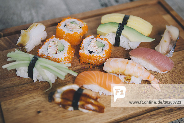 Hochwinkelansicht verschiedener Sushi auf dem Schneidebrett