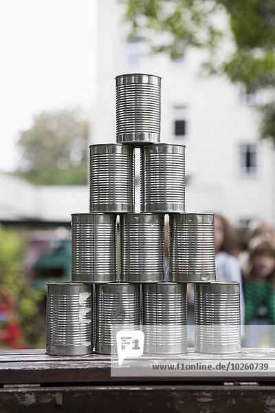 Metallic tin stacked on table outdoors