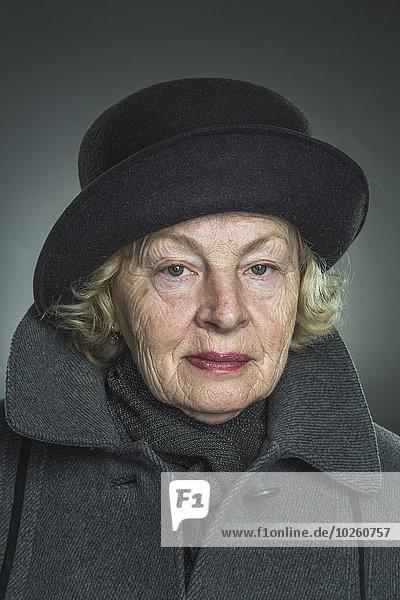 Porträt einer älteren Frau mit Hut und Jacke vor grauem Hintergrund