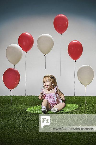 Fröhliches Mädchen sitzt auf Gras mit roten und weißen Luftballons in der Luft.