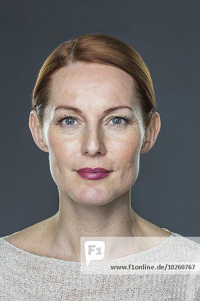 Porträt einer reifen Frau vor grauem Hintergrund