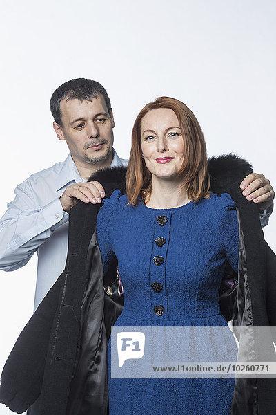 Mann unterstützt lächelnde Frau im Wintermantel vor weißem Hintergrund