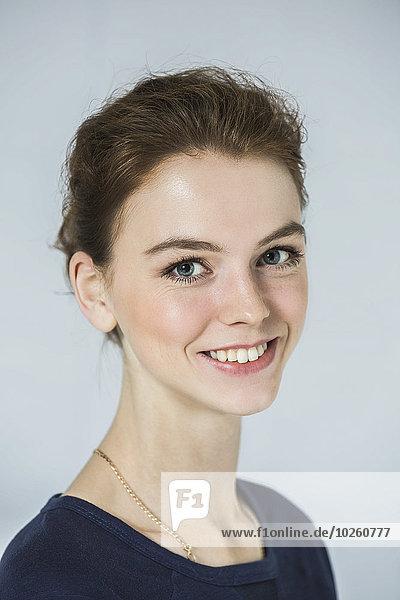 Nahaufnahme des Porträts einer fröhlich schönen Frau vor grauem Hintergrund