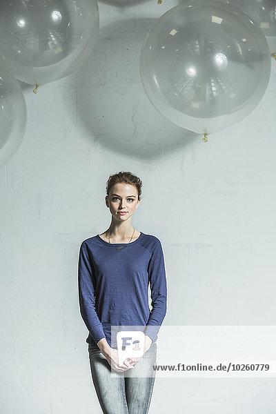 Porträt einer selbstbewussten Frau  die mit den Händen auf weißem Grund steht.