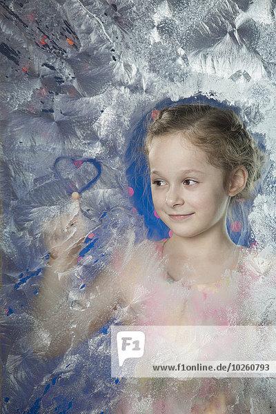 Lächelndes Mädchen macht Herzform auf gefrorenem Glas