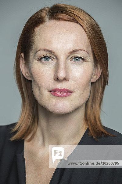Porträt einer selbstbewussten reifen Frau vor grauem Hintergrund