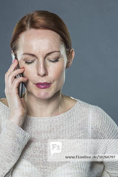 Gestresste reife Frau mit Handy vor grauem Hintergrund