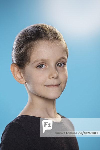 Porträt des süßen Mädchens lächelnd auf blauem Hintergrund