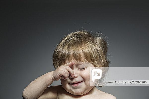 Süßer Junge reibt sich die Augen vor grauem Hintergrund.