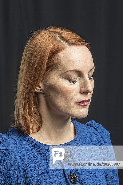 Reife Frau mit geschlossenen Augen vor schwarzem Hintergrund