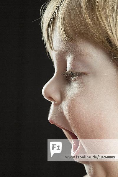 Süßer Junge mit geöffnetem Mund vor schwarzem Hintergrund