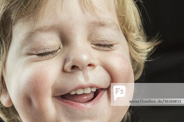 Nahaufnahme des fröhlichen Jungen mit geschlossenen Augen über schwarzem Hintergrund