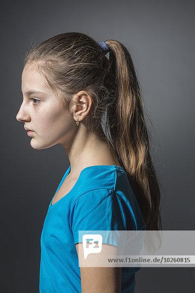 Seitenansicht des traurigen Mädchens vor grauem Hintergrund
