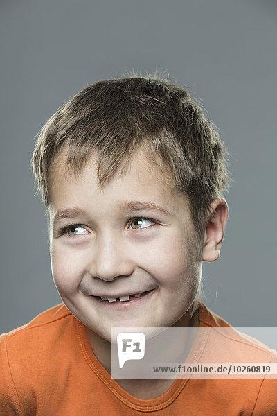 Glücklicher Junge schaut weg vor grauem Hintergrund