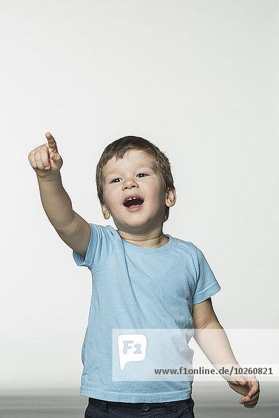 Fröhlicher Junge zeigt auf weißen Hintergrund