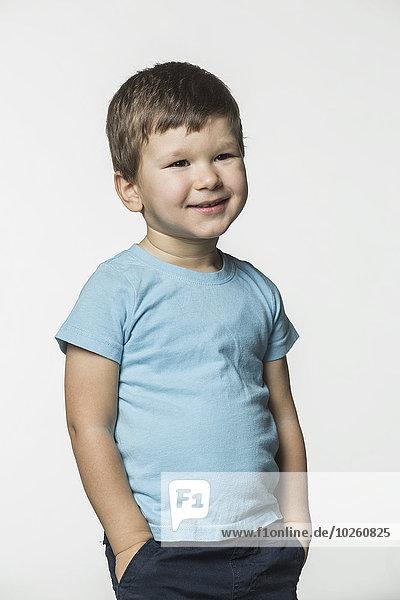Glücklicher Junge stehend mit Händen in Taschen vor weißem Hintergrund