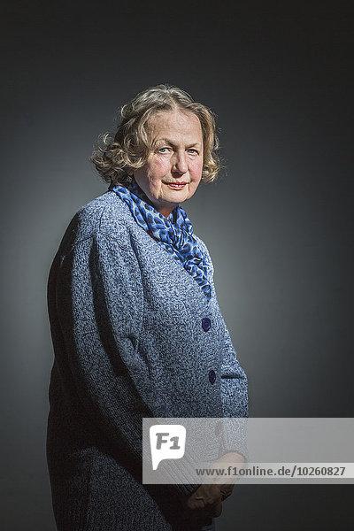Porträt einer älteren Frau  die mit den Händen vor grauem Hintergrund steht.