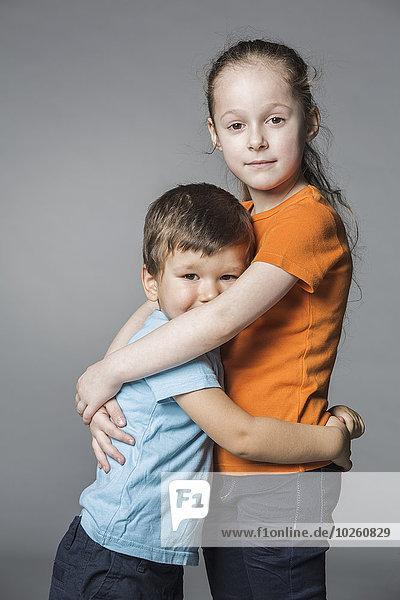 Porträt von süßen Geschwistern  die sich vor grauem Hintergrund umarmen.