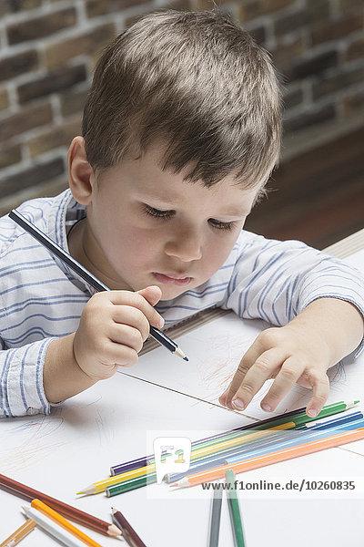 Jungenmalerei auf Papier am Tisch im Haus