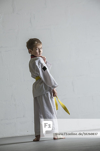 Porträt des Karatejungen an der weißen Wand stehend