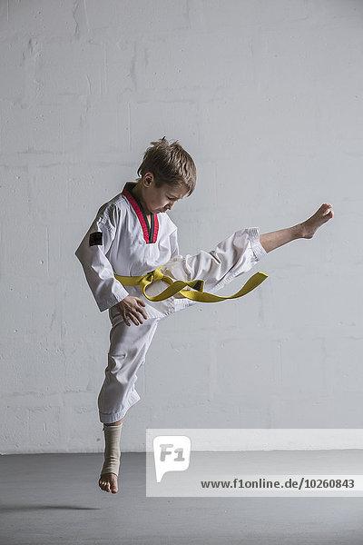 Karatejunge tritt in die Luft gegen die weiße Wand