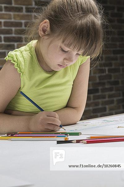 Mädchenzeichnung am Tisch gegen die Ziegelwand im Haus