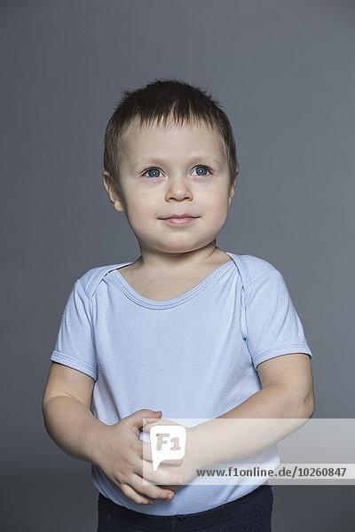 Nachdenklicher Junge mit Händen auf dem Bauch stehend vor grauem Hintergrund