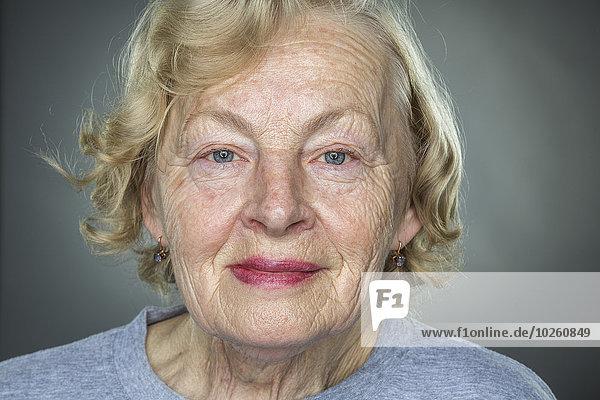 Nahaufnahme der lächelnden Seniorin vor grauem Hintergrund